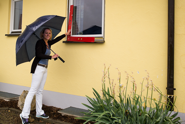 Auch bei Regenwetter ist Bianca Richter mit der roten Meßlatte und Digitalkamera unterwegs, um ein Fotoaufmaß, anhand des Fassadenfotos mit der Aufmaßsoftware Bildaufmaß aus dem Hause C.A.T.S.-Soft zu erstellen.