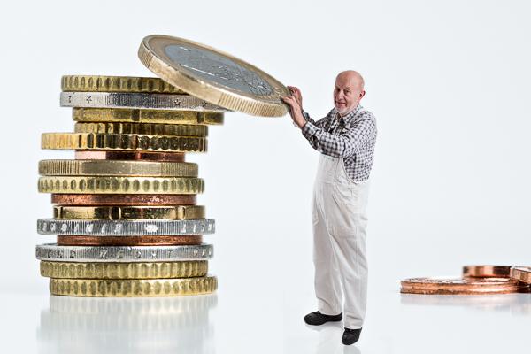 Maler legt Euro-Münze auf Geldstapel