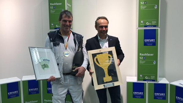 Der neue Deutsche Meister im Rauhfaser-Schnelltapezieren: Michael Rapp (l.) bekommt von Frank Seemann (Leiter Marketing Erfurt & Sohn) Pokal und Gewinn überreicht.